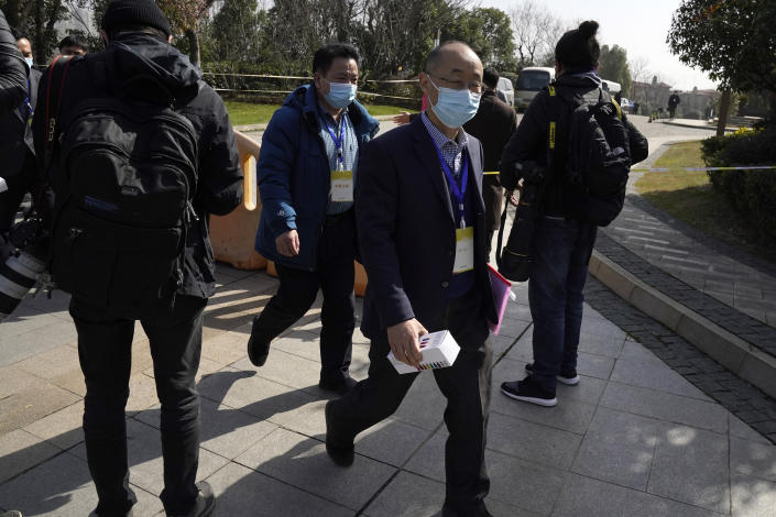 """Chinese attendees, some wearing tags which reads """"Expert Team,"""" leave from a conference area of a hotel where the World Health Organization team of researchers are staying in Wuhan in central China's Hubei province on Friday, Jan. 29, 2021. World Health Organization experts are to begin face-to-face meetings with their Chinese counterparts Friday in the central city of Wuhan at the start of the team's long-awaited fact-finding mission into the origins of the coronavirus. (AP Photo/Ng Han Guan)"""