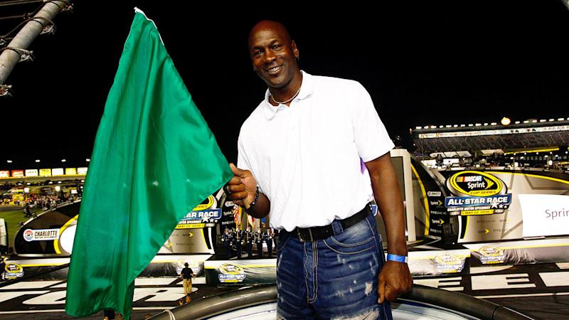 Pictured here, Michael Jordan waves a flag at a NASCAR race.