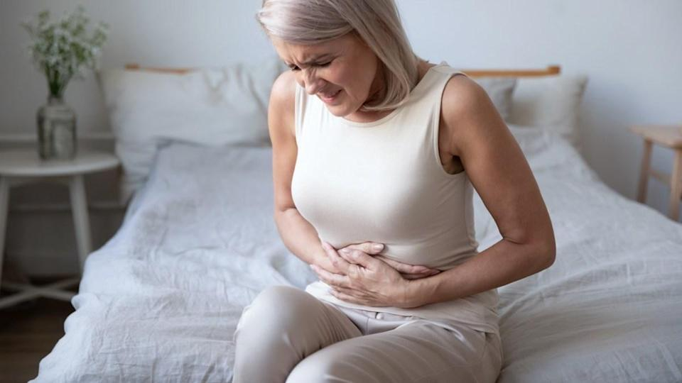 Unhealthy mature woman holding belly, feeling discomfort