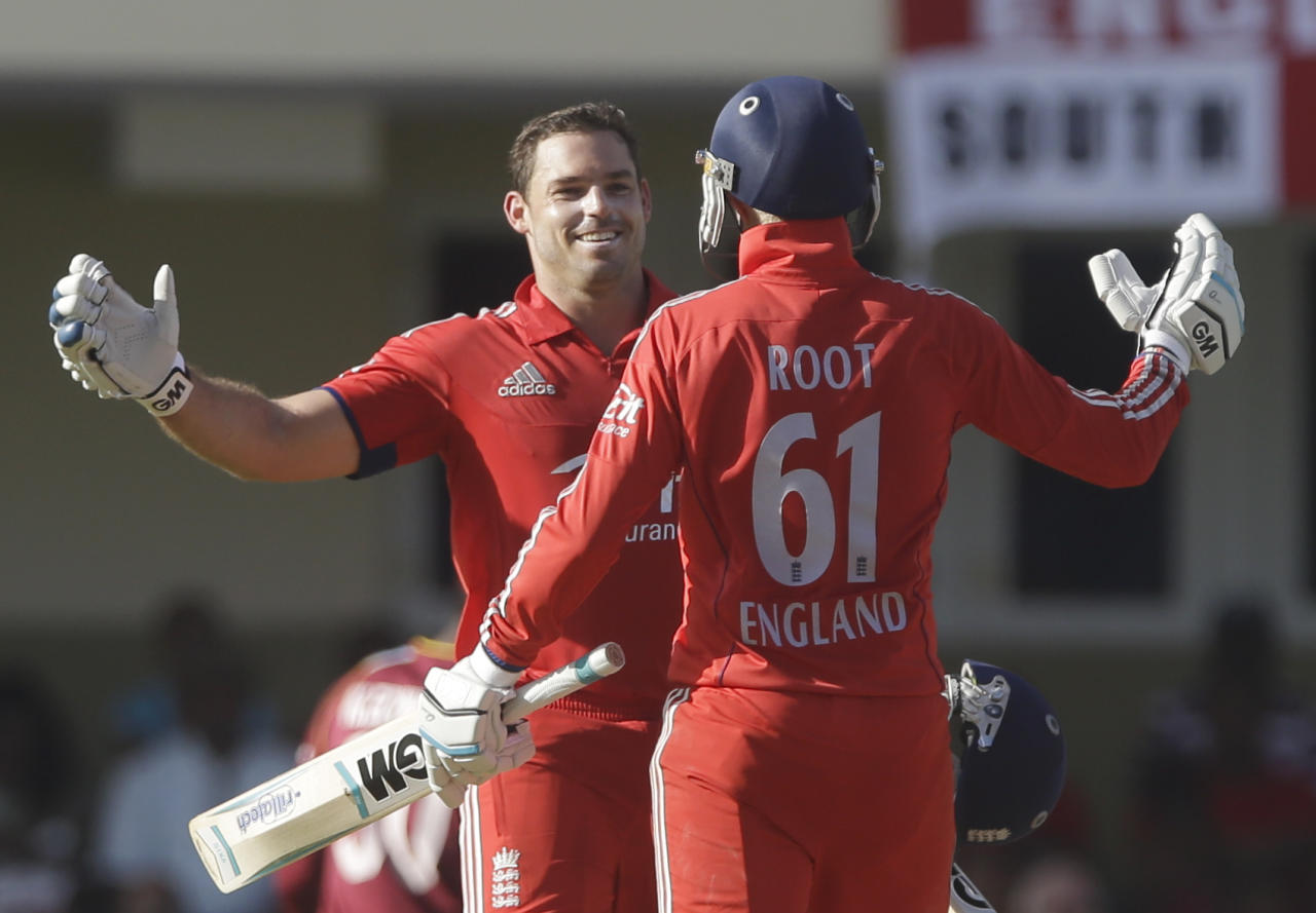 England's Michael Lumb, left, celebrates after he scored a century with Joe Root during their first one-day international cricket match against West Indies at the Sir Vivian Richards Cricket Ground in St. John's, Antigua, Friday, Feb. 28, 2014. (AP Photo/Ricardo Mazalan)