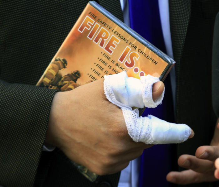Newark Mayor Cory Booker has a bandaged right hand as he holds a children's fire safety video given to him by a well-wisher in Newark, N.J., Friday, April 13, 2012, where he was credited with rescuing a neighbor Thursday from a fire. Booker said Friday he feared for his life as he helped rescue a neighbor from a fire before firefighters arrived. He described how he returned home Thursday night and saw his neighbor's home engulfed in flames. The woman Booker helped save is in stable condition. (AP Photo/Mel Evans)