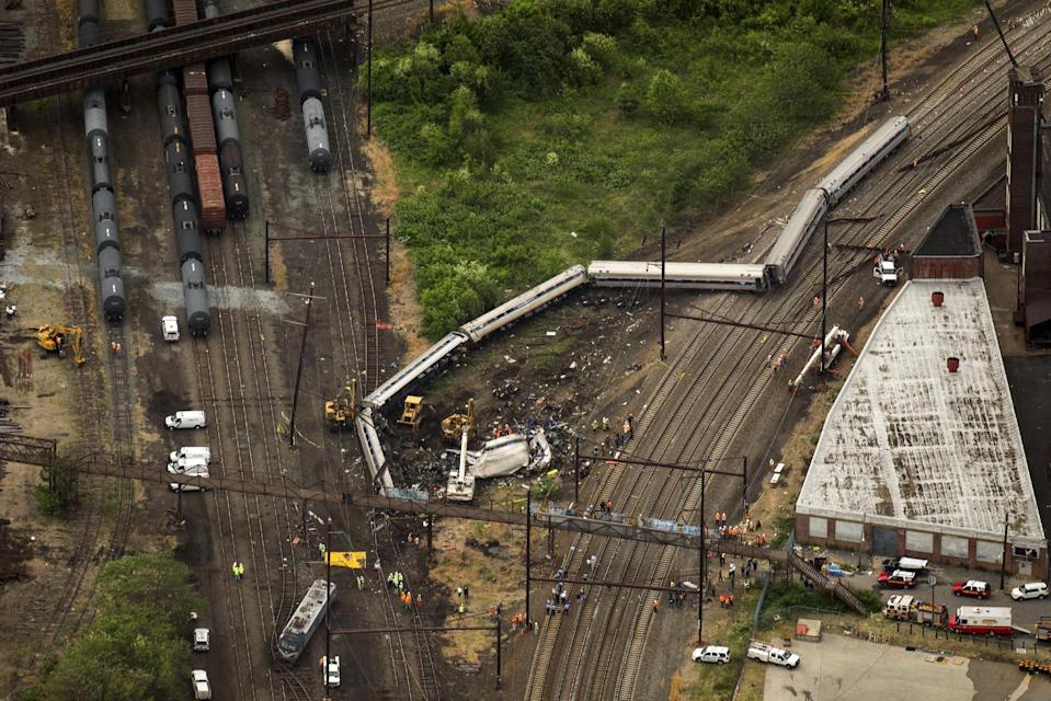 Emergency workers look through the remains of a derailed Amtrak train in Philadelphia, Pennsylvania May 13, 2015. Rescue workers on Wednesday sifted through twisted metal and debris from the wreck of the Amtrak train that derailed in Philadelphia, killing six people and injuring scores of others, as investigators began reviewing data to determine the cause of an accident. REUTERS/Lucas Jackson