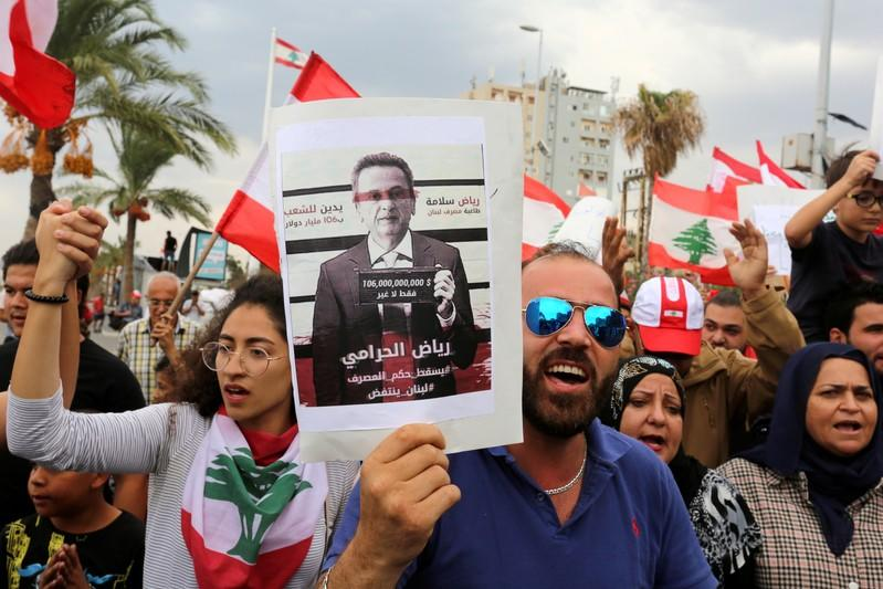 FILE PHOTO: Demonstrators carry Lebanese flags and a banner depicting Lebanon's Central Bank Governor Riad Salameh during an anti-government protest in the southern city of Tyre