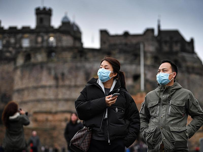 Tourists wear face masks as they visit Edinburgh Castle on 24 January, 2020: Getty