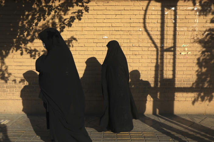 Women wearing protective face masks to help prevent the spread of the coronavirus walk on a sidewalk in southern Tehran, Iran, Tuesday, July 20, 2021. Iran on Tuesday broke another record in the country's daily new coronavirus cases, even as Tehran and its surroundings went into lockdown, a week-long measure imposed amid another surge in the pandemic. (AP Photo/Vahid Salemi)