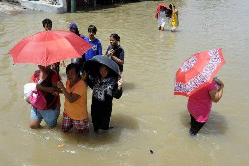 Local residents are seen wading through murky floodwaters in the aftermath of Typhoon Nesat and Nalgae in Calumpit, north of the capital Manila. Philippine authorities said on Sunday the death toll from two typhoons that pummelled the country two weeks ago had reached 101, with tens of thousands of people still displaced by massive flooding