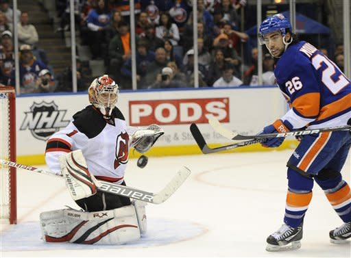 New York Islanders' Matt Moulson (26) watches New Jersey Devils goalie Johan Hedberg (1) deflect the puck away from the goal in the first period of an NHL hockey game on Saturday, March 10, 2012, in Uniondale, N.Y. (AP Photo/Kathy Kmonicek)