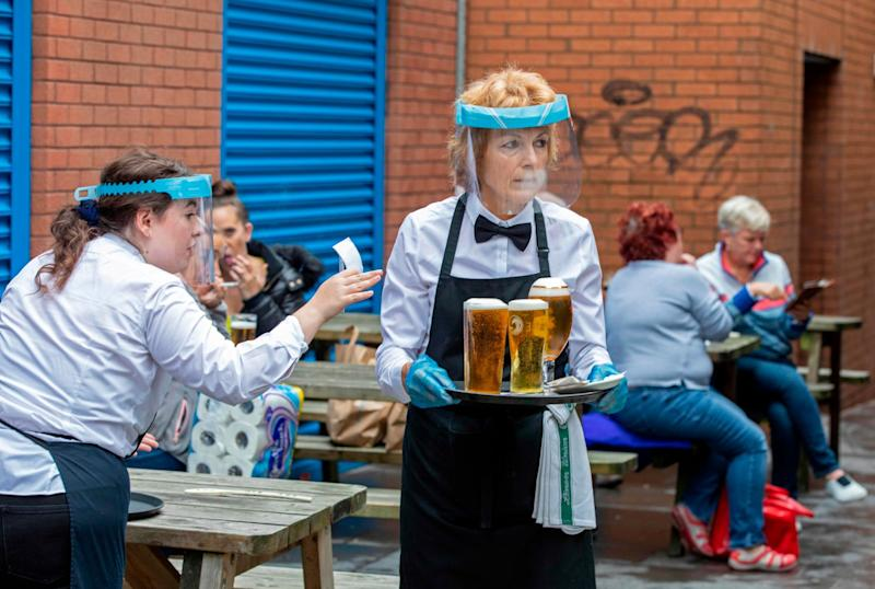 Staff wearing PPE serve people enjoying a drink in Belfast city centre on Friday: AFP/Getty