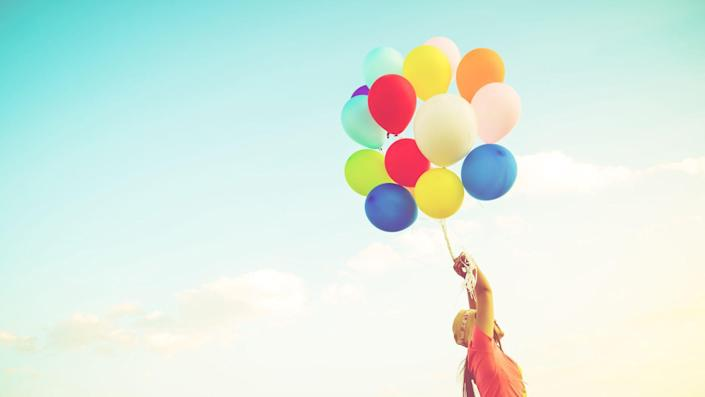 Girl hand holding multicolor balloons done with a retro instagram filter effect, concept of happy birth day in summer and wedding honeymoon party, Vintage color tone style.