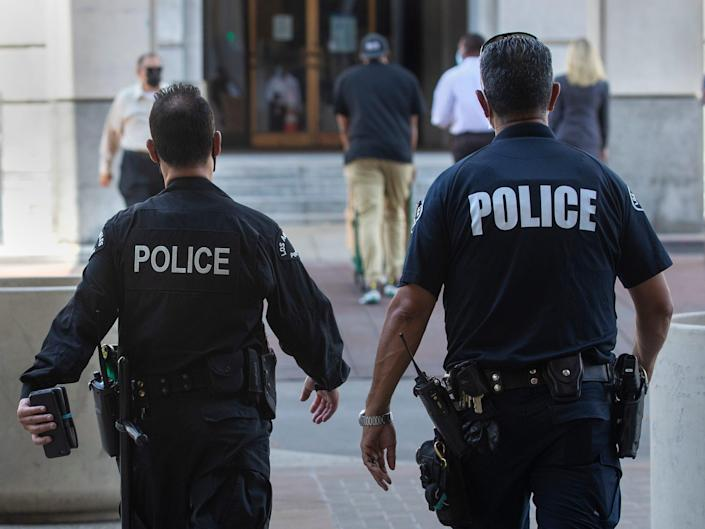Members of the LAPD make their way towards City Hall in downtown Los Angeles.
