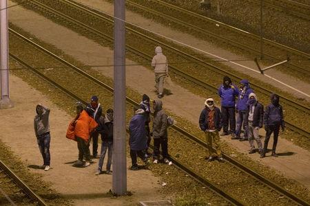 Migrants walk on the railway tracks of the freight shuttle leading to the entrance of the Channel Tunnel in Calais, France, October 14, 2015. REUTERS/Philippe Wojazer
