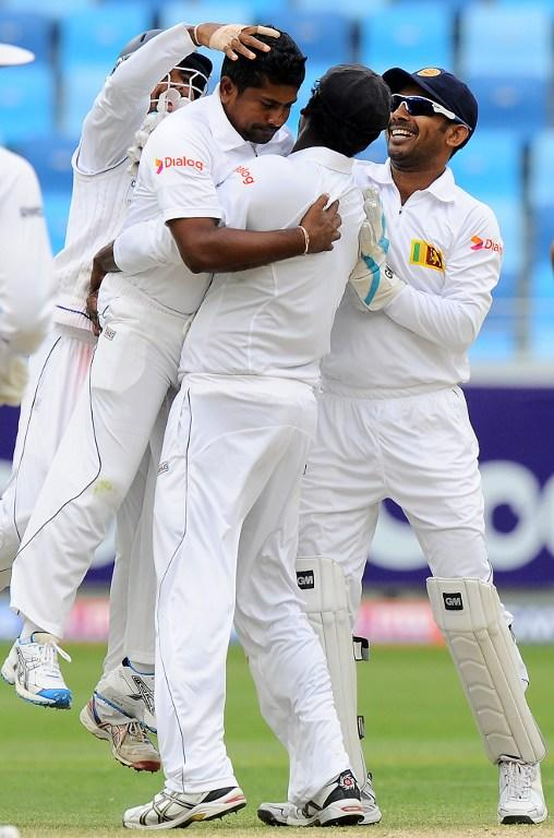 Sri Lankan bowler Rangana Herath (L) with teammates celebrates the dismissal of Pakistan batsman Misbah-ul-Haq during the fourth day of the second cricket Test match between Pakistan and Sri Lanka at the Dubai International Cricket Stadium in Dubai on January 11, 2014.  AFP PHOTO/Ishara S. KODIKARA