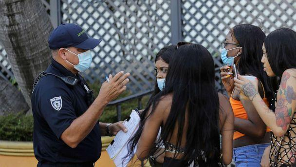 PHOTO: Luis Negron, a Miami Beach code compliance officer, left, talks with women along Ocean Drive about wearing a protective face mask amid the coronavirus pandemic, July 24, 2020, in Miami Beach, Fla. (Lynne Sladky/AP)