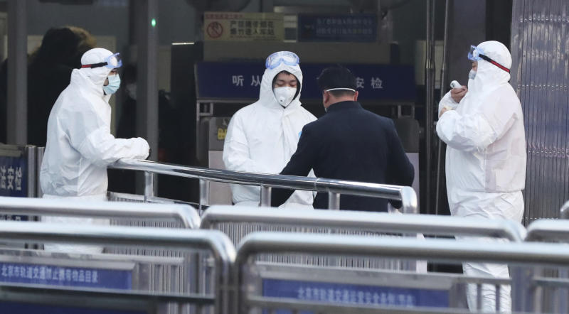 Security staffs clad in protective clothing check the body temperature of passengers at the entrance of a subway station in Beijing. Source: AP