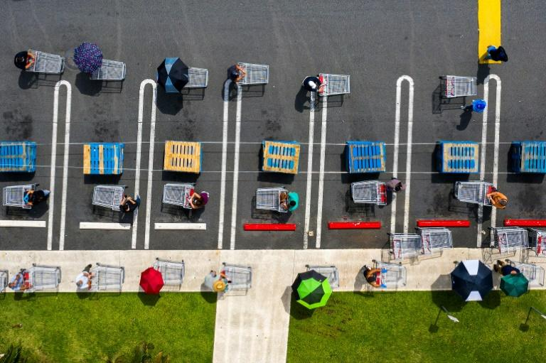 People keep their distance as they queue at a store in Carolina, Puerto Rico (AFP Photo/Ricardo ARDUENGO)