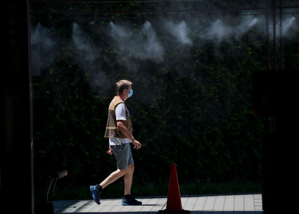 <p>A photographer wearing a face mask to prevent the spread of COVID-19 walks under a disinfection system installed at the International Press Center for the 2020 Tokyo Olympics in Tokyo on July 21, 2021. (Photo by Yuri CORTEZ / AFP) </p>