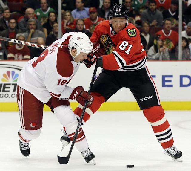 Phoenix Coyotes' David Moss, left, and Chicago Blackhawks' Marian Hossa battle for the puck during the first period of an NHL hockey game in Chicago, Thursday, Nov. 14, 2013. (AP Photo/Nam Y. Huh)
