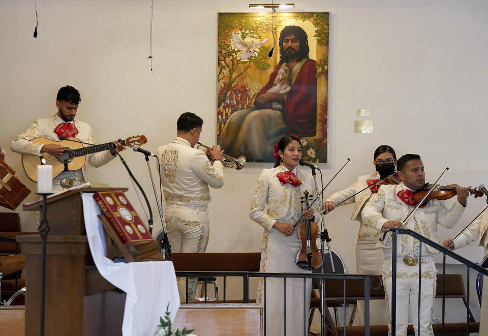 """The band Mariachi Herencia de Cuco Del Cid members, from left, Daniel Piñuelas, Cesar Galvez, Sarina Grijalva, Christina Vazquez and Daniel Rodriguez preform for parishioners during a morning Mass at Most Holy Trinity Parish Sunday, Aug. 18, 2021 in Tucson. """"When you sing or there's music offered up to God, it's like praying but it's more powerful,"""" Rodriguez says. """"For us to be a driving force through our music, to inspire people to come back and stay at Mass, that's really powerful."""" (AP Photo/Darryl Webb)"""
