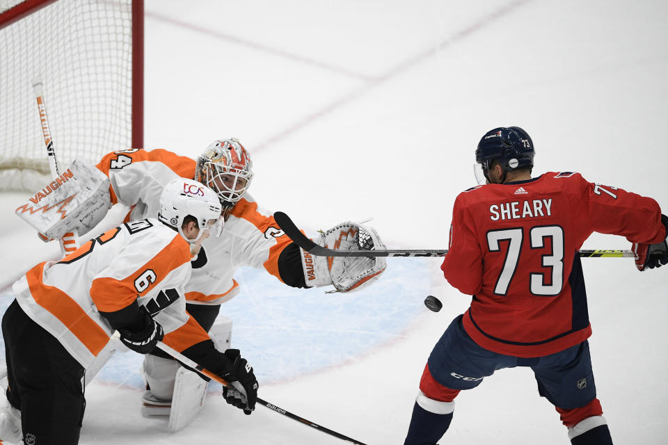 Philadelphia Flyers goaltender Alex Lyon (34) and defenseman Travis Sanheim (6) work for the puck against Washington Capitals left wing Conor Sheary (73) during the first period of an NHL hockey game Saturday, May 8, 2021, in Washington. (AP Photo/Nick Wass)