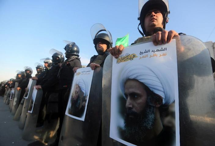 Iraqi police stand guard holding posters of prominent Shiite cleric Nimr al-Nimr during a demonstration in Baghdad by supporters of Iraqi Shiite cleric Moqtada al-Sadr against Nimr's execution by Saudi authorities (AFP Photo/Ahmad Al-Rubaye)