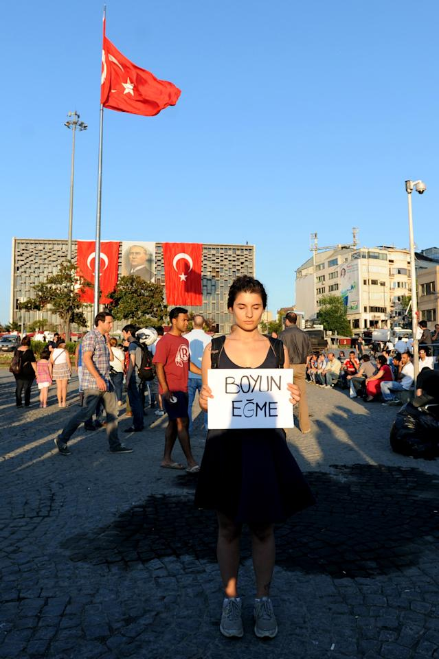 ISTANBUL TURKEY - JUNE 18: (TURKEY OUT) Demonstrators face Ataturk Cultural Center during a silent protest at Taksim Square, on June 18, 2013 in Istanbul, Turkey. Erdem Gunduz acquired the nickname 'The Standing Man' following his silent eight hour vigil outside the cultural centre where a giant portrait of the country's founder, Mustafa Kemal Ataturk, hangs. Gunduz has become the new symbol of anti-goverment protests and his actions have sparked similar silent protests around the country. (Photo by Burak Kara/Getty Images)