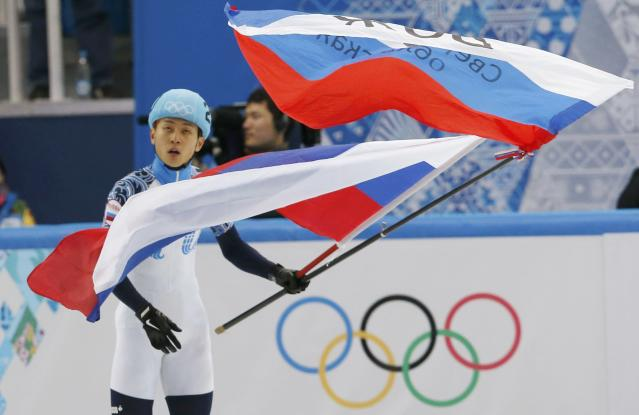 Victor An of Russia waves flags after he won the men's 1,000 metres short track speed skating final event at the Iceberg Skating Palace during the 2014 Sochi Winter Olympics February 15, 2014. REUTERS/Alexander Demianchuk (RUSSIA - Tags: OLYMPICS SPORT SPEED SKATING)
