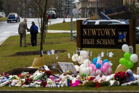 A student is consoled after he placed flowers on a memorial at the entrance to Newtown High School in Newtown, Connecticut December 18, 2012.     REUTERS/Lucas Jackson
