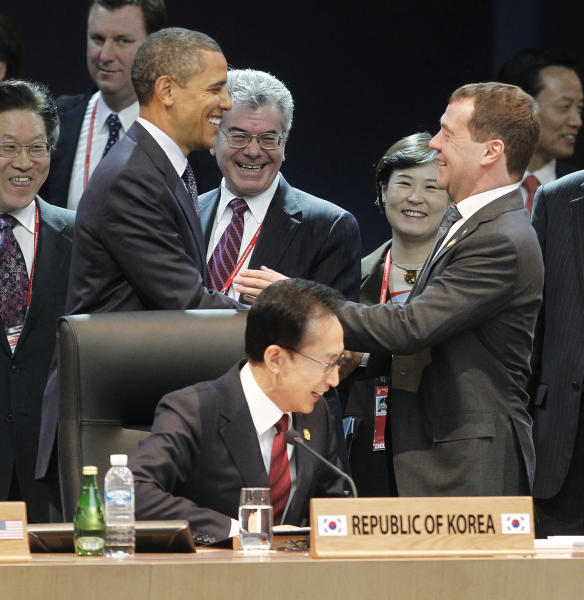 U.S. President Barack Obama, left, smiles with Russian President Dmitry Medvedev, right, as they attend the opening plenary session at the Nuclear Security Summit at the Coex Center, in Seoul, South Korea, Tuesday, March 27, 2012. Sitting in the center is South Korean President Lee Myung-bak. (AP Photo/Pablo Martinez Monsivais)