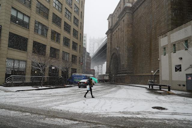 <p>A woman walks the DUMBO section of Brooklyn, New York as the snow gets heavier as a spring storm moved through the area on March 21, 2018. (Photo: Gordon Donovan/Yahoo News) </p>
