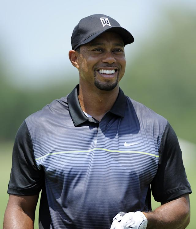 Tiger Woods smiles on the driving range during a practice round for the Quicken Loans National golf tournament, Tuesday, June 24, 2014, in Bethesda, Md. (AP Photo/Nick Wass)