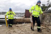 A Coastguard picks up debris in Swanage, Dorset, from beach huts that have been lost as a result from storm Alex.