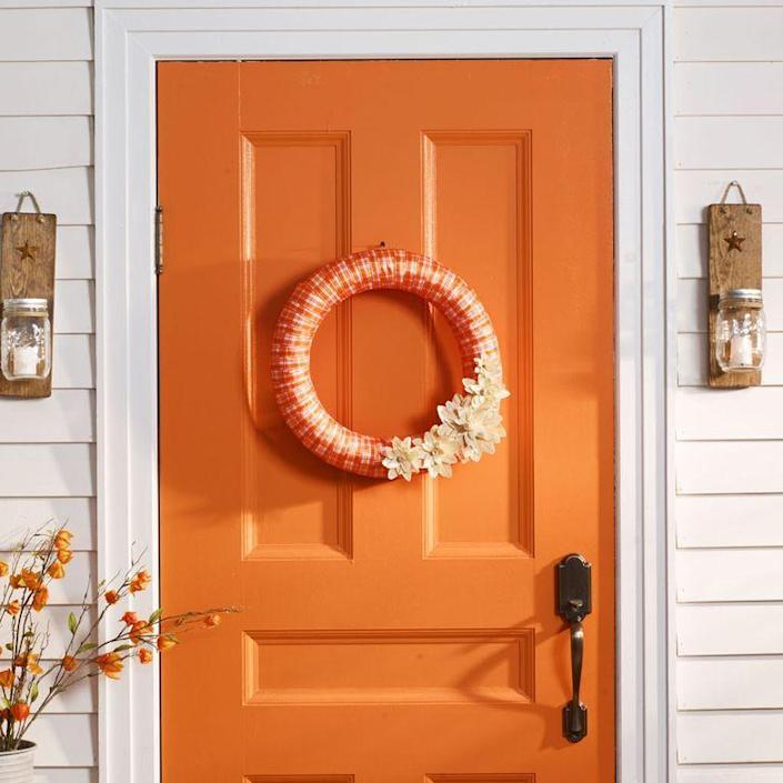 """<p>Embellish the bottom of this festive fall wreath with flowers fashioned from dried corn husks.</p><p><strong>1. </strong>Wrap plaid ribbon around <span>18-inch</span> wreath form; secure with hot glue.</p><p><strong>2. </strong>For flowers, soak corn husks in room-temperature water for two minutes; remove and blot excess water. To make a few petals at once, accordion-fold corn husk into <span>1-inch</span>-wide sections, then cut out <span>1-inch</span> teardrop-shaped petal. Repeat as needed and to make <span>1</span>½-inch and <span>2</span>½-inch petals.</p><p><strong>3. </strong>Cut a <span>1-inch</span>-wide corn husk strip, fold in half lengthwise, roll into tight swirl, and hot-glue onto a small cardboard circle. Hot-glue on petals, working big to small, back to front.</p><p><strong>4. </strong>Hot-glue flowers to wreath.</p><p><strong>What You'll Need: </strong><a href=""""https://www.amazon.com/Homeford-FHV000033544-Checkered-Christmas-Ribbon/dp/B013PWLU2Q?tag=syn-yahoo-20&ascsubtag=%5Bartid%7C10070.g.2488%5Bsrc%7Cyahoo-us"""" rel=""""nofollow noopener"""" target=""""_blank"""" data-ylk=""""slk:Orange plaid ribbon"""" class=""""link rapid-noclick-resp"""">Orange plaid ribbon</a> ($12, Amazon)</p>"""