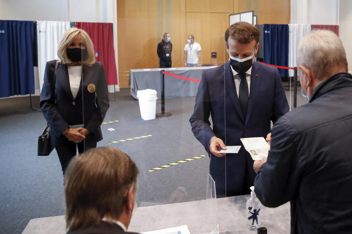 French President Emmanuel Macron shows his passport while his wife Brigitte waits during the first round of French regional and departmental elections, in Le Touquet-Paris-Plage, northern France, Sunday, June 20, 2021. The elections for leadership councils of France's 13 regions, from Brittany to Burgundy to the French Riviera, are primarily about local issues like transportation, schools and infrastructure. But leading politicians are using them as a platform to test ideas and win followers ahead of the April presidential election. (Christian Hartmann/Pool via AP)