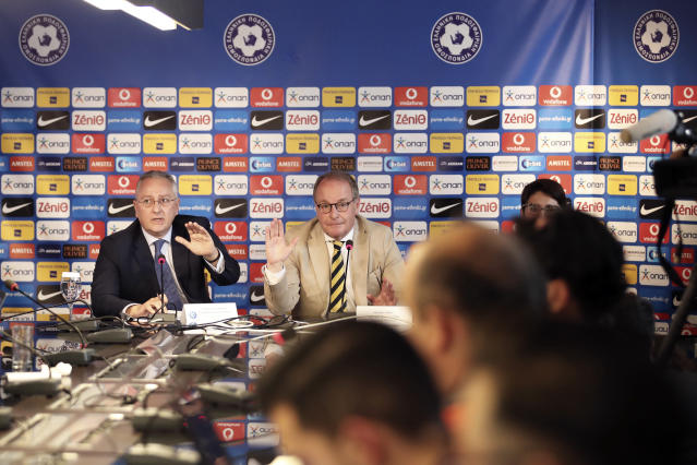 Austrian Herbert Huebel, center, chairman of the FIFA monitoring committee for the Hellenic Football Federation answers a question during a press conference in Athens, Wednesday, March 14, 2018. FIFA has sent a delegation to Greece to discuss the country's soccer crisis, after the government indefinitely suspended top league matches. The suspension followed a pitch invasion by the gun-toting owner of PAOK Thessaloniki Sunday after a late goal for his team was disallowed by the referee. (AP Photo/Petros Giannakouris)