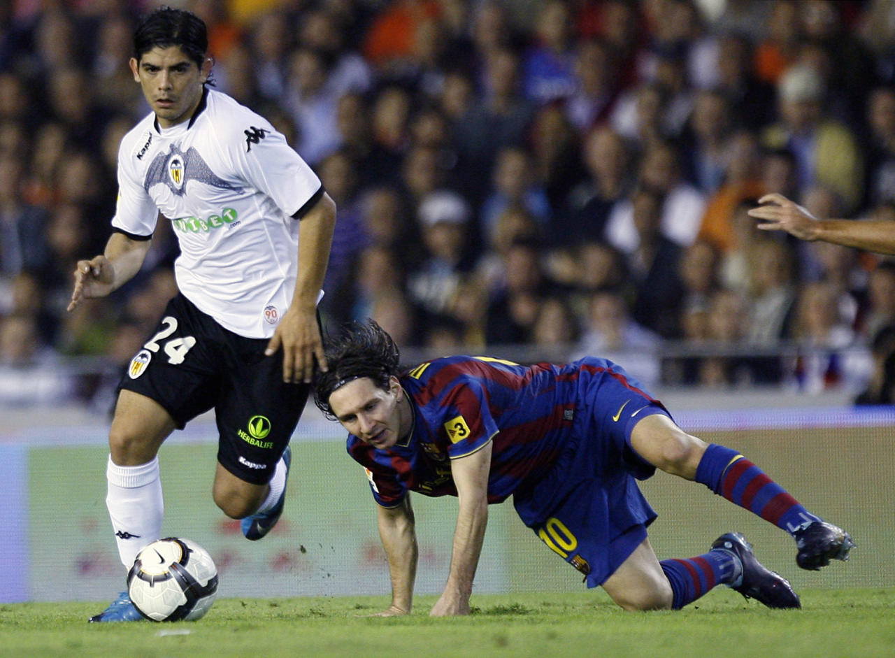 Valencia's Ever Banega from Argentina, left duels for the ball with Barcelona's Lionel Messi of Argentina during a Spanish La Liga soccer match at the Mestalla stadium in Valencia, Saturday, Oct. 17, 2009. After showing an irregular performance in Spain's Valencia, Banega seems to have finally fitted in the team's scheme and is considered its leader for the 2012 season. (AP Photo/Alberto Saiz)