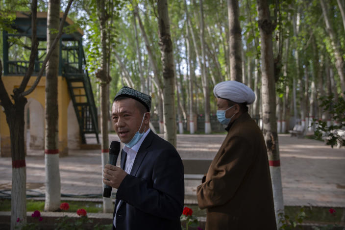 Mamat Juma, left, imam of the Id Kah Mosque, speaks to foreign journalists during a government organized visit at the mosque in Kashgar in western China's Xinjiang Uyghur Autonomous Region on April 19, 2021. Under the weight of official policies, the future of Islam appears precarious in Xinjiang, a remote region facing Central Asia in China's northwest corner. Outside observers say scores of mosques have been demolished, which Beijing denies, and locals say the number of worshippers is on the decline. (AP Photo/Mark Schiefelbein)