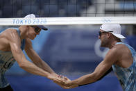 Tri Bourne, left, of the United States, celebrates with teammate Jacob Gibb, after winning a men's beach volleyball match against Switzerland at the 2020 Summer Olympics, Wednesday, July 28, 2021, in Tokyo, Japan. (AP Photo/Felipe Dana)