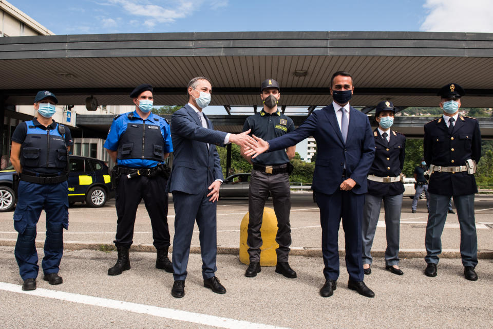 Italian Minister of Foreign Affairs Luigi Di Maio, right, and Swiss Federal Councillor and Minister of Foreign Affairs Ignazio Cassis, left, wear a face masks to protect against the coronavirus as they meet at the Chiasso Brogeda customs border in Chiasso, Switzerland, Tuesday, June 16, 2020. (Alessandro Crinari/Keystone/Pool via AP)