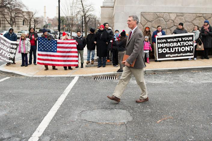 Rep. Erik Paulsen (R-Minn.) walks by immigration protesters on his way to one of the buses outside the Rayburn House Office Building as House Republicans prepare to head to Hershey, Pa., for their retreat with Senate Republicans on Jan. 14, 2015.