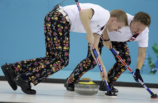 Norway's Haavard Vad Petersson, left, and Torger Nergaard sweep ahead of the rock during men's curling competition against Canada at the 2014 Winter Olympics, Friday, Feb. 14, 2014, in Sochi, Russia