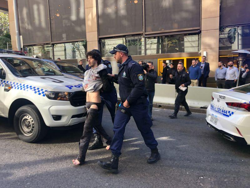 Sydney stabbing suspect Mert Ney is seen here being lead away by NSW Police officers in the CBD.