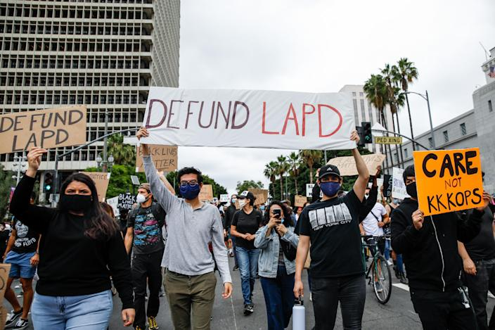A variety of signs, including Defund LAPD, were held high, among about 1,000 people gathered to protest the death of George Floyd and in support of Black Lives Matter, in downtown, Los Angeles, CA, on Friday, June 5, 2020. (Jay L. Clendenin/Los Angeles Times via Getty Images)