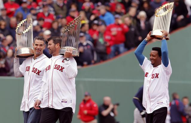 Former Red Sox players, from left, Mike Lowell, Jason Varitek and Pedro Martinez hold World Series trophies during pre-game ceremonies before a baseball game against the Milwaukee Brewers on Opening Day at Fenway Park in Boston, Friday, April 4, 2014. (AP Photo/Michael Dwyer)