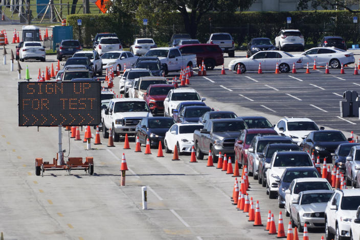 FILE - In this Jan. 5, 2021, file photo, cars line up for COVID-19 testing outside Hard Rock Stadium in Miami Gardens, Fla. Coronavirus deaths and cases per day in the U.S. dropped markedly over the past couple of weeks but are still running at alarmingly high levels, and the effort to snuff out COVID-19 is becoming an ever more urgent race between the vaccine and the mutating virus. (AP Photo/Wilfredo Lee, File)