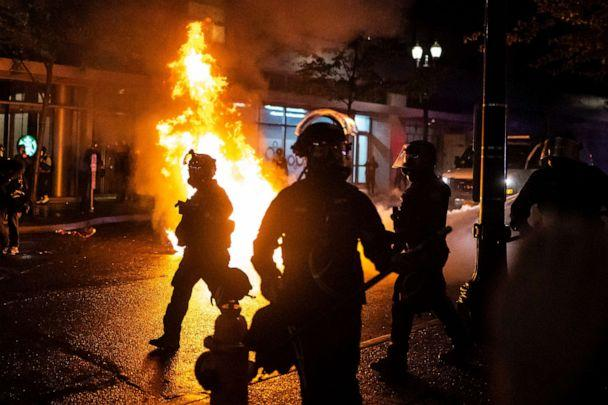 PHOTO: Portland police walk past a fire started by a Molotov cocktail thrown at police, Sept. 23, 2020, in Portland, Oregon. (Nathan Howard/Getty Images)