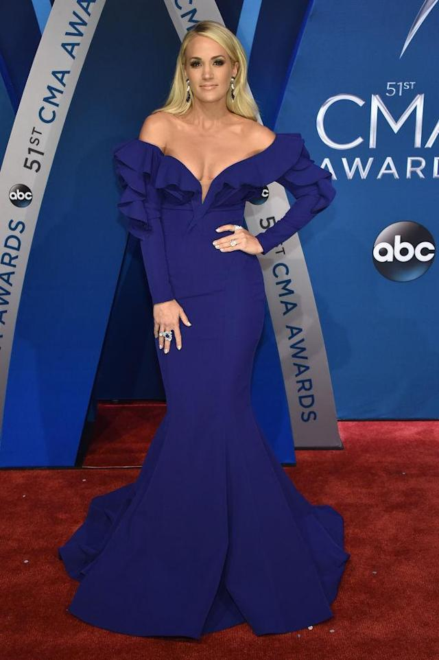 <p>For the 10th year in a row, Underwood hosted the event alongside Brad Paisley. The singer had multiple outfit changes, but she turned it out with her first ensemble, in a deep shade of purple. The off-the-shoulder silhouette showed some skin, but she covered up with long sleeves and a floor-sweeping hemline. (Photo: Getty Images) </p>