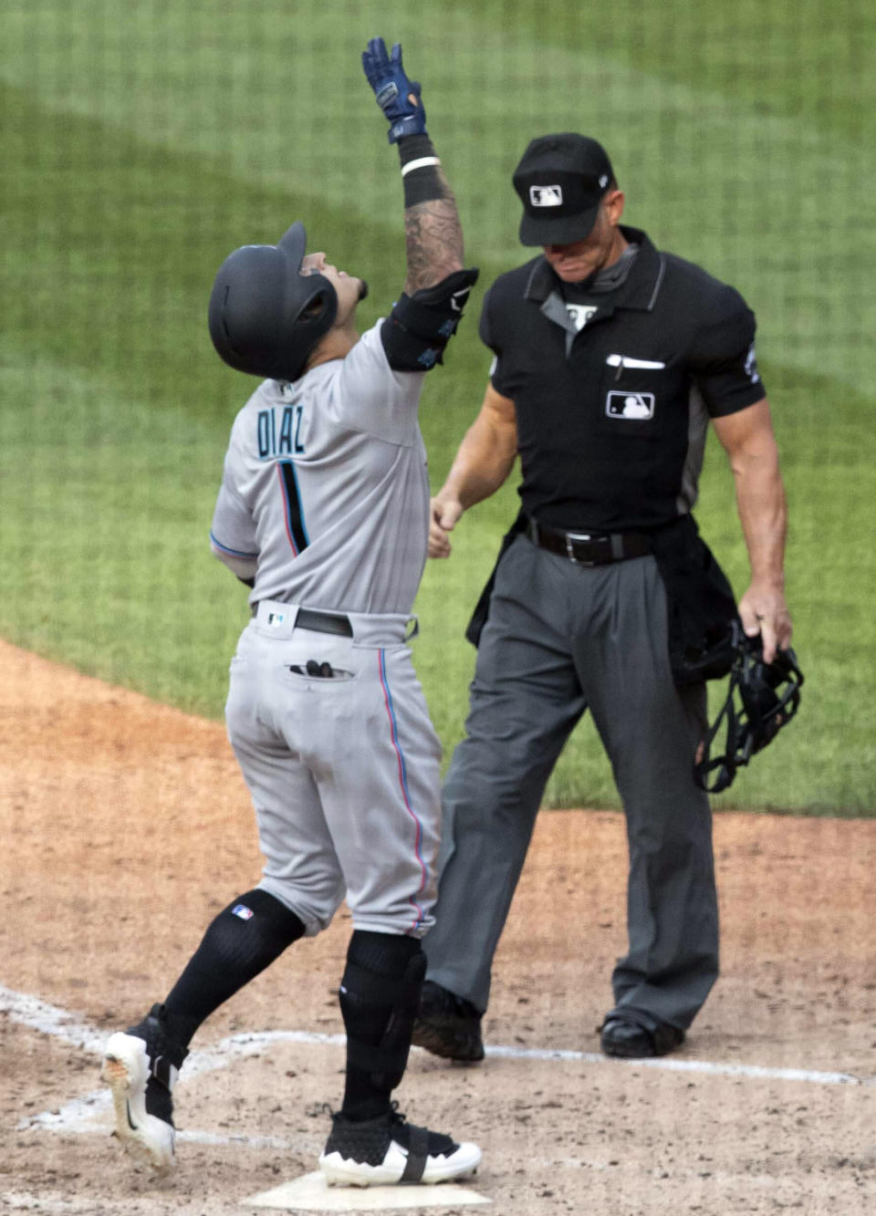 Miami Marlins' Isan Diaz, left, reacts as he comes into home plate after hitting a home run in his major league debut during the sixth inning of a baseball game against the New York Mets, Monday, Aug. 5, 2019, in New York. (AP Photo/Mary Altaffer)