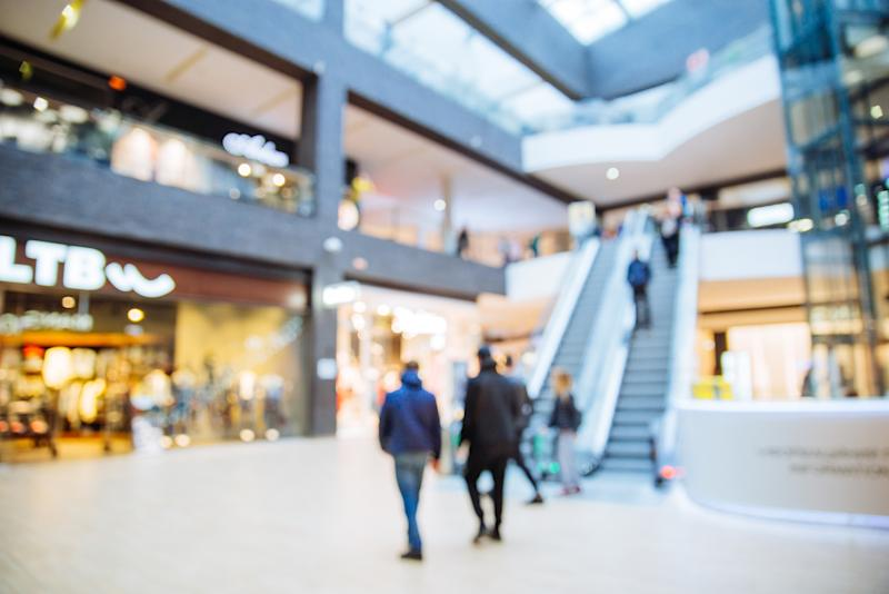 People wandering around in an indoor shopping mall.