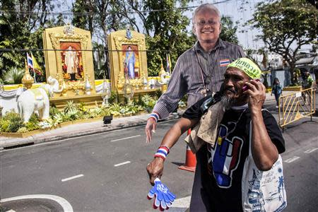 An anti-government protester carries a cardboard cut-out of anti-government protest leader Suthep Thaugsuban outside the residential house of Prem Tinsulanonda, chief of the Privy Council and the king's advisor, in Bangkok January 24, 2014. REUTERS/Nir Elias