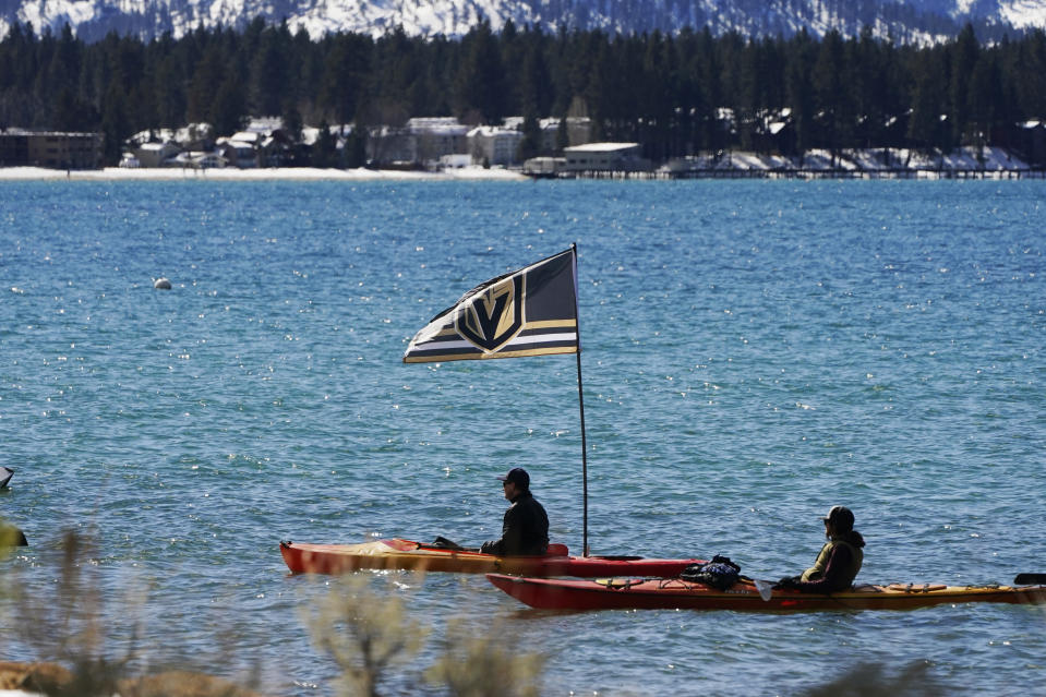 A Vegas Golden Knights flag flies from a kayak at Lake Tahoe offshore from the site of an outdoor NHL hockey game between the Golden Knights and the Colorado Avalanche at Stateline, Nev., Saturday, Feb. 20, 2021. (AP Photo/Rich Pedroncelli))